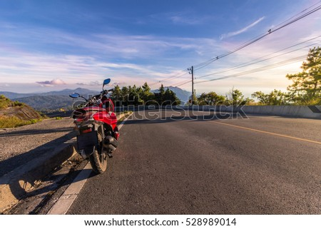 Motorcycle, serpentine road, mountains on background and blue sky on sunset. Active lifestyle and vacation concept