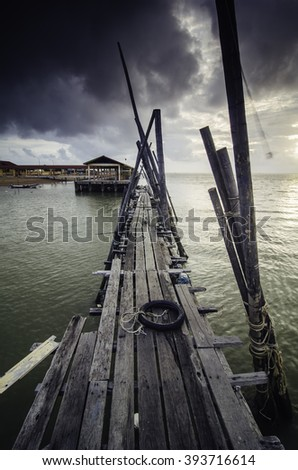 motorcycle tyre on wooden fisherman jetty with dramatic dark cloud and sea water ripple during sunrise - stock photo