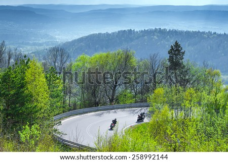 motorcycles riders going down, passing sharp curves, on European mountains roads - stock photo