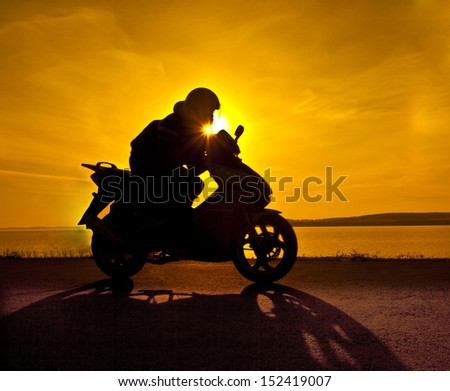 motorcyclist against yellow sunset Copy space for inscription