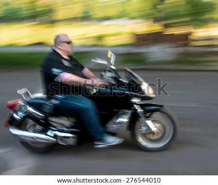 Motorcyclist in motion going down the street . Intentional motion blur - stock photo