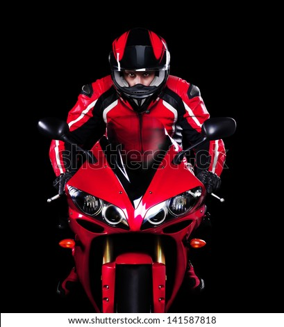Motorcyclist in red equipment and helmet on black background - stock photo