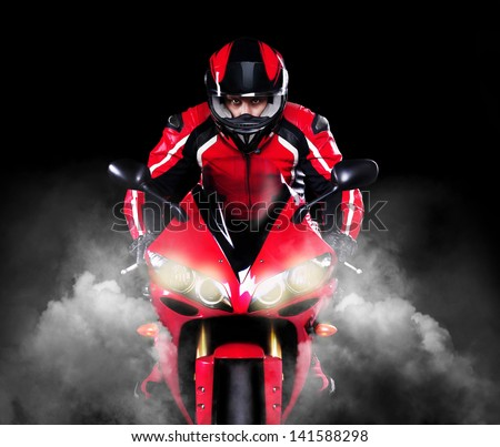Motorcyclist in red equipment and helmet riding motorbike with headlights on  over black background - stock photo