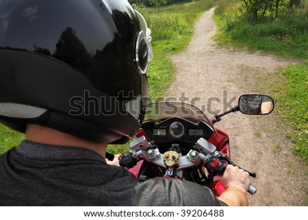 motorcyclist on country road, shoulder view - stock photo