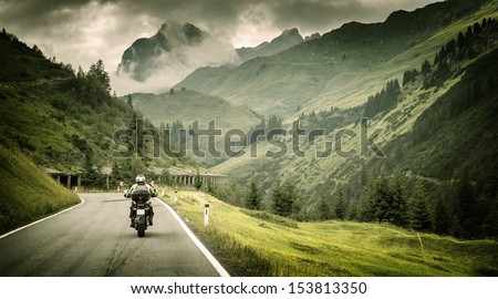 Motorcyclist on mountainous highway, cold overcast weather, Europe, Austria, Alps, extreme sport, active lifestyle, adventure touring concept - stock photo