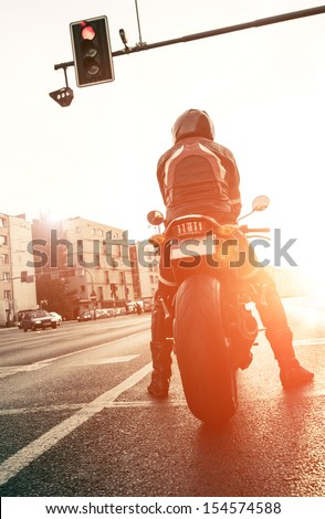 motorcyclist on the road with the setting sun - stock photo