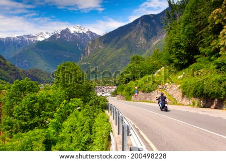 Motorcyclist riding in the Switzerland Alps. - stock photo