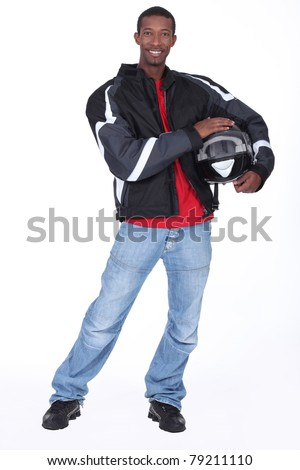 Motorcyclist wearing black jacket and helmet - stock photo
