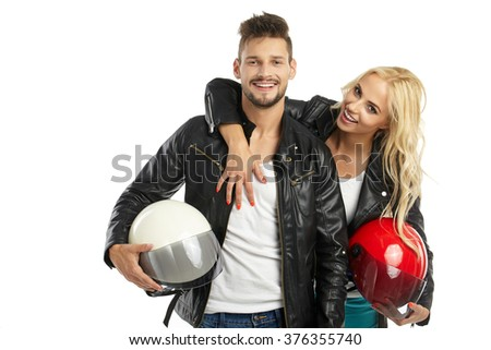 motorcyclists couple with helmets in hand. Studio shoot - stock photo
