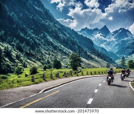 Motorcyclists on mountainous road, enjoying tour along Alps, summertime activities, wonderful mountain landscape, extreme vacation concept - stock photo