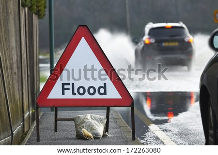 Motorist driving through flood waters with warning sign in foreground - stock photo