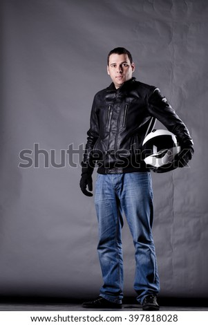 motorist with a helmet, leather jacket and jeans, on grunge background with harsh lighting