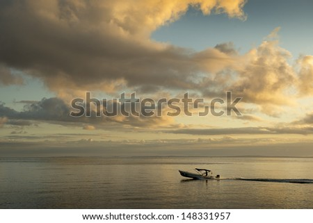 Motorized boat leaving the port of Ankify after sunrise. Ankify, Madagascar.
