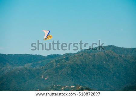 Motorized Hang Glider Flying Over Mountain Hills On Blue Clear Sunny Sky Background.