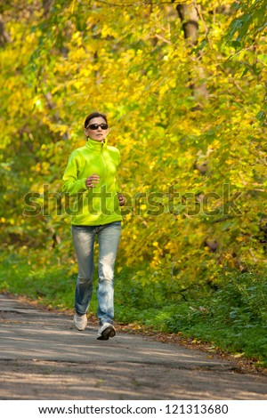 Moture woman jogging in autumn forest. - stock photo