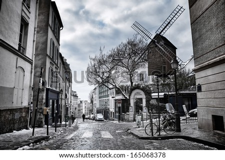 Moulin de la Galette in Montmartre (Paris, France) with melting snow on the side of the street - stock photo