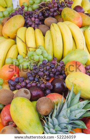 Mound of mixed fruit including green and purple grapes, bananas, mangoes, kiwis, plums, papayas and pineapple vertical - stock photo