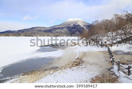 Mount Akan, active volcano in winter with white snow at the peak and foreground of frozen lake Akan and hot spring