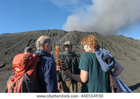 Mount Bromo Indonesia - Jun 13, 2016 : Tenggerese man selling flower to tourist at Bromo crater foothill. Mount Bromo one of an active volcano that most visited by tourist in East Java Indonesia. - stock photo