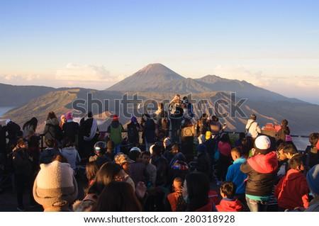 MOUNT BROMO, INDONESIA - JUNE 28, 2014: Undefined tourists watching sunrise over Bromo volcano, Tengger Semeru National Park, East Java, Indonesia on June 26, 2014 - stock photo
