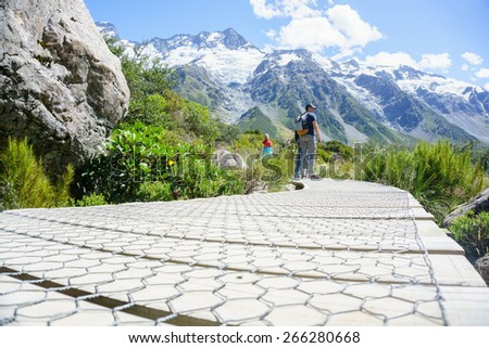 MOUNT COOK, NEW ZEALAND - February 16; People hiking, pausing to observe the natural beauty on one of the great New Zealand walks February 16,2015 at Mount Cook, New Zealand. Hookers Track  - stock photo