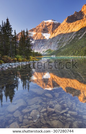Mount Edith Cavell reflected in Cavell Lake in Jasper National Park, Canada. Photographed at sunrise. - stock photo