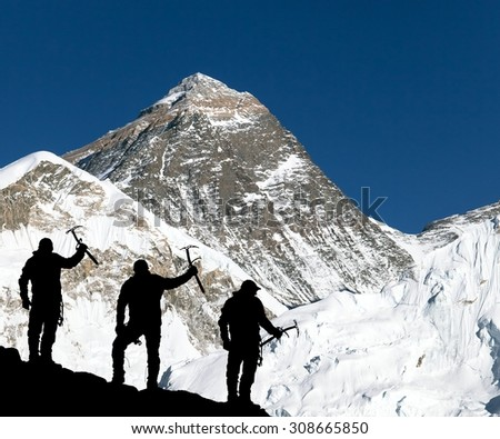 Mount Everest from Kala Patthar from Kala Patthar and silhouette of climbing men with ice axe in hand - trek to everest base camp - Nepal  - stock photo