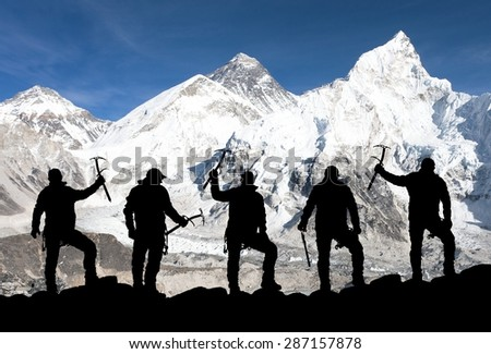 Mount Everest, Lhotse, Nuptse and icefall Khumbu from Kala Patthar and silhouette of climbing men with ice axe in hand - trek to everest base camp - Nepal  - stock photo