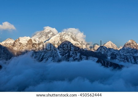 Mount Everest view from Gokyo Ri. Picturesque mountain valley filled with curly clouds at sunset. Dramatic snowy peak of Everest rise above river of clouds. Sagarmatha National Park, Nepal, Himalayas. - stock photo
