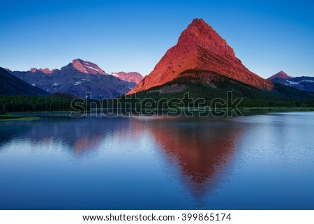 Mount Grinnell takes on a warm glow from the light of a rising sun in Montana's Glacier National Park. The view is of Swiftcurrent Lake situated in front of the Many Glacier Hotel.
