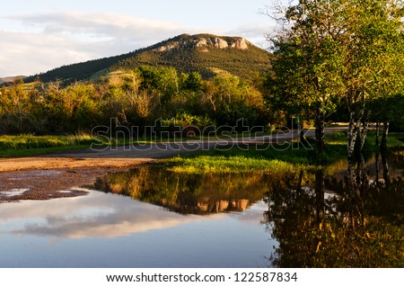 Mount Helena can be seen from many parts of Helena, Montana.  This reflection is not a normal one as it occurred because of a bit of spring flooding. - stock photo