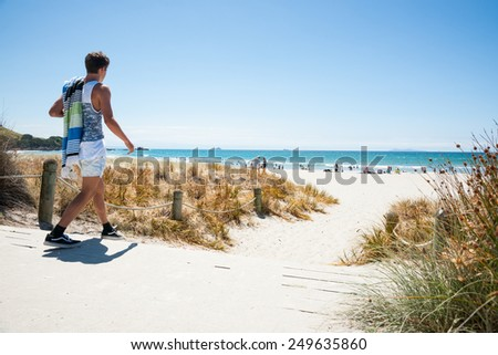 MOUNT MAUNGANUI, NEW ZEALAND-JANUARY 22; youth walks to beach on hot summer day, carrying his towel on January 22, 2015  at Mount Maunganui Mount, New Zealand. the beaches are key summer destinations. - stock photo