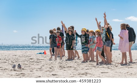 MOUNT MAUNGANUI, NEW ZEALAND - NOVEMBER 4; Nippers coaching event on Mount Maunganui Beach respond to their coach raising arms signaling they know answer November 4, 2012 Mount Maunganui, New Zealand