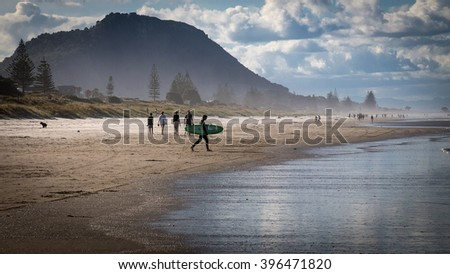 MOUNT MAUNGANUI, NEW ZEALAND - OCTOBER 10, 2013:  Sunbathers and surfers gather at Mount Maunganui beach near Tauranga, one of the most popular holiday resort areas in New Zealand. - stock photo