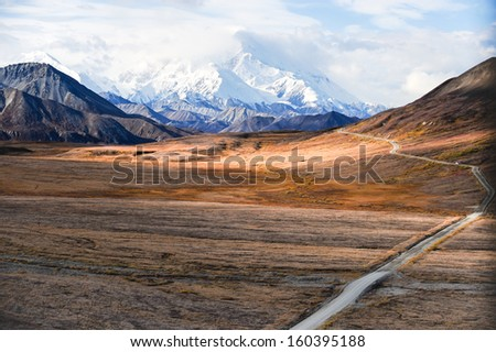 Mount McKinley's snowy peak with the park road and tundra in the foreground, Denali National Park, Alaska, US.  Mount McKinley is the highest peak in North America. - stock photo