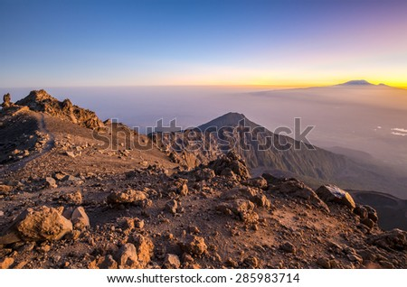 Mount Meru with Kilimanjaro in the distance, near Arusha in Tanzania. Africa. Mt Meru is located 60 kilometres west of Mount Kilimanjaro. - stock photo