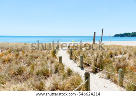 Mount Ocean beach on warm summer day sand path leading to sea through dunes.