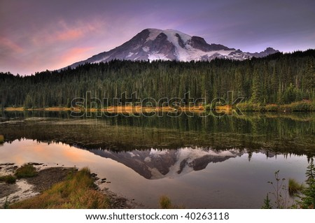 Mount Rainier reflected across the reflection lakes at dusk under a dramatic sky