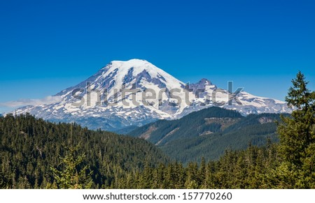Mount Rainier towers over the surrounding mountains sitting at an elevation of 14,411 ft. It is considered to be one of the world's most dangerous volcanoes. - stock photo