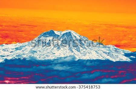 Mount Rainier with fresh snow and low clouds, aerial view, Washington