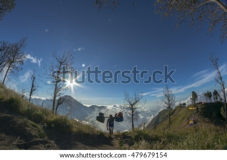 MOUNT RINJANI, LOMBOK, INDONESIA - JUNE 12, 2015 : Unidentified porter on his way to the camp site. Rijani mountain is one of the highest mountains in Indonesia