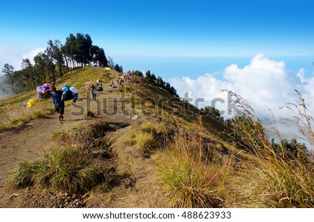 MOUNT RINJANI, LOMBOK, INDONESIA - SEPT 18, 2016: A group of mountaineers walking on Sembalun camp site. Rinjani mountain is one of the highest mountains in Indonesia