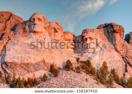 Mount Rushmore National Park in the Black Hills South Dakota during a warm sunrise with clear blue sky morning. High Dynamic Range. / Mount Rushmore National Park