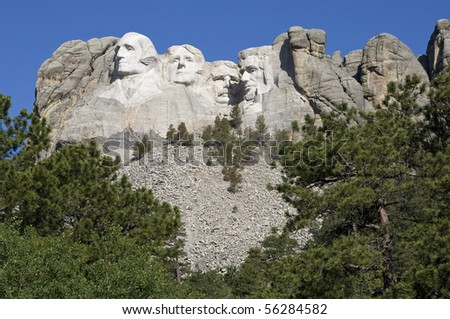 Mount Rushmore with green trees in foreground - stock photo