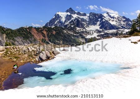 Mount Shuksan Blue Pool Woman Green Shirt Summer Artist Point Mount Baker Highway Snow Mountain Grass Trees - stock photo