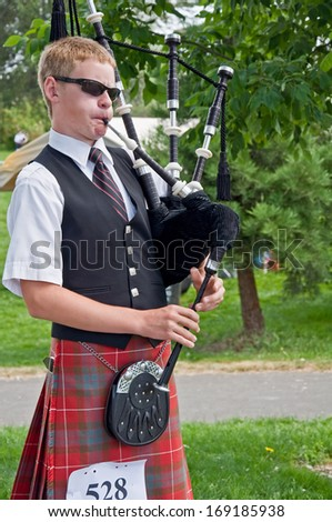 MOUNT VERNON, WA/USA - JULY 9, 2010: teenage boy participates in the annual Scottish Highland games event, playing a bagpipe to bring cultural awareness to the community. - stock photo