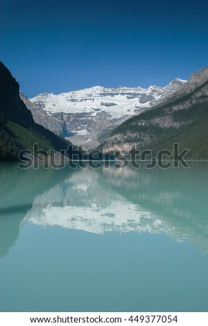 Mount Victoria and the Victoria Glacier under a cloudless sky reflected in the calm water of Lake Louise in Banff National Park, Alberta, Canada. - stock photo