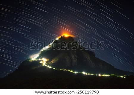 Mountain Adam's Peak (Sri Pada) illuminated at night with starry sky on the background. Sri Lanka - stock photo