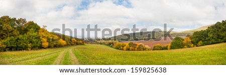 Mountain autumn landscape panorama with colorful forest and lush green meadow - stock photo