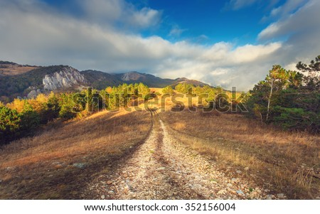 Mountain autumn landscape with road at sunset. Low clouds. Nature background - stock photo
